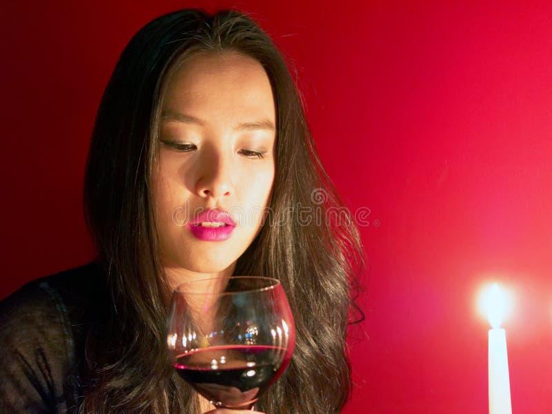 De mooie vrouw staart in kaarslicht aangezien zij de dag van Valentine ` s voorziet stock afbeelding