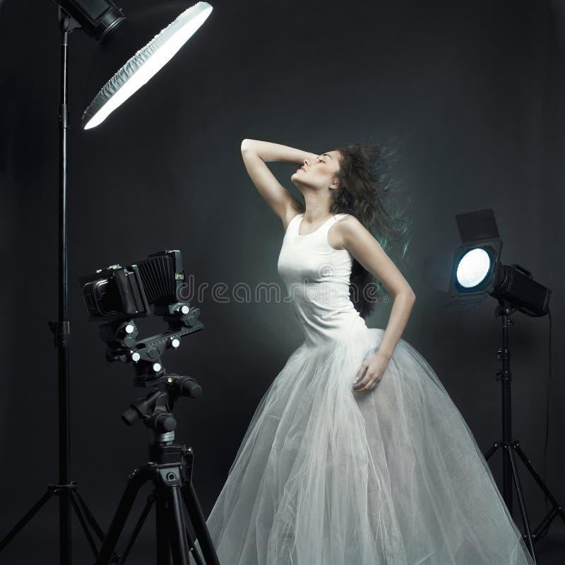 De mooie vrouw stelt in foto-studio stock foto's