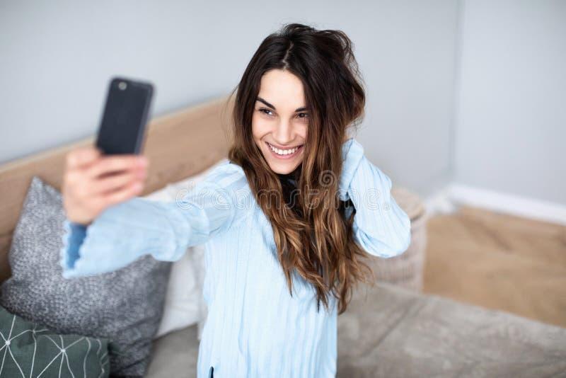 De mooie vrouw thuis op de laag selfie op celtelefoon stock fotografie