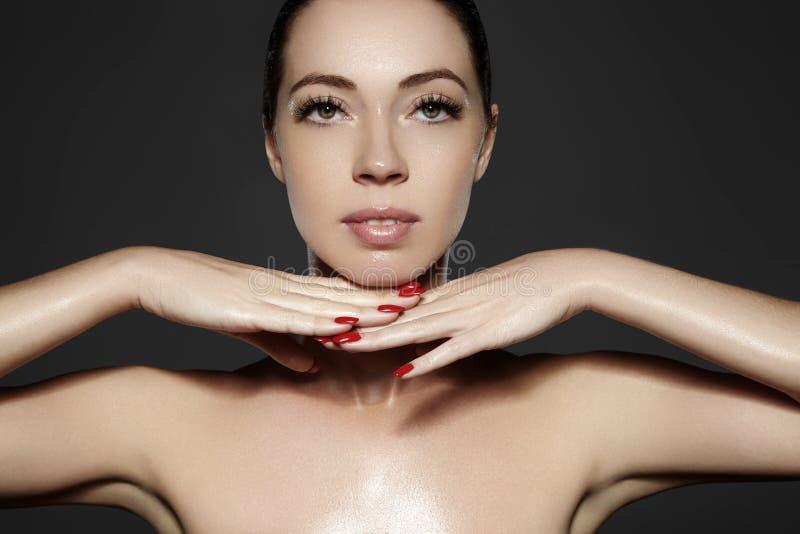 De mooie vrouw toont haar erfectgezicht met maniersamenstelling Extreme wimpers, mollige lippen, schone huid Fresh spa kijk stock foto's