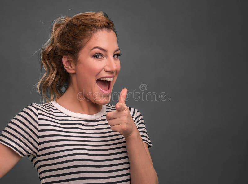 De mooie vrouw toont op u die op een grijze achtergrond stellen stock afbeeldingen