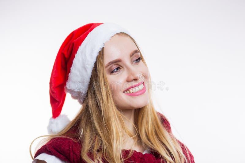 De mooie vrouw van de blondekerstman in rode hoed die en op witte achtergrond glimlachen lachen stock foto
