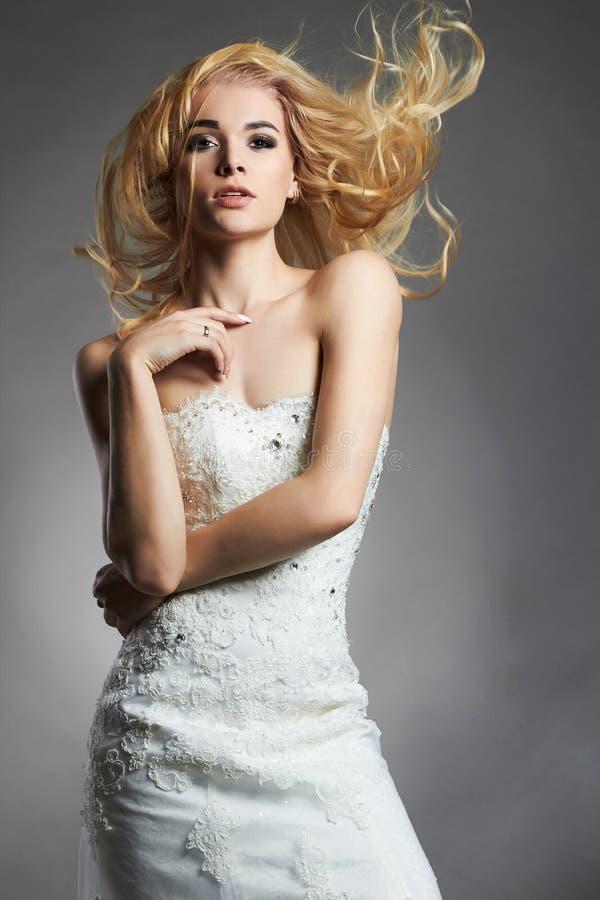 De mooie vrouw van de blondebruid in huwelijkskleding stock afbeeldingen
