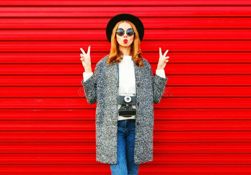 De mooie vrouw van het manierportret met het retro camera stellen op een rood stock afbeelding