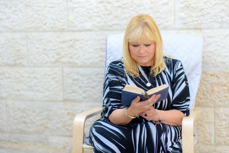 De mooie vrouw van het middenleeftijdsblonde in openlucht het boekzitting van de terraslezing in leunstoel royalty-vrije stock afbeeldingen