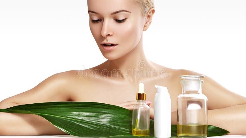 De mooie vrouw vraagt organische schoonheidsmiddel en oliën schoonheid aan Kuuroord en wellness Schone huid, glanzend haar Gezond stock afbeeldingen
