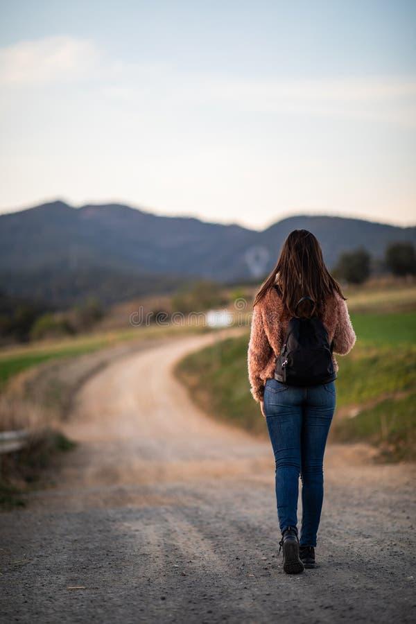 De mooie vrouw wandeling over een brug met de weg en de bergen vertroebelden op de achtergrond stock afbeeldingen