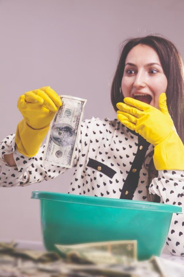De mooie vrouw wast Amerikaanse dollarrekening als symbool van het witwassen en legalisatie van geld Selectieve nadruk op hand en royalty-vrije stock foto's