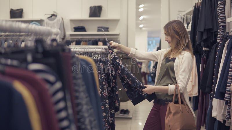 De mooie vrouw zoekt kleren in de kledingswinkel royalty-vrije stock foto