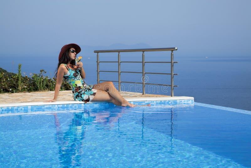 De mooie vrouw zonnebaadt bij de oneindigheidspool stock afbeeldingen