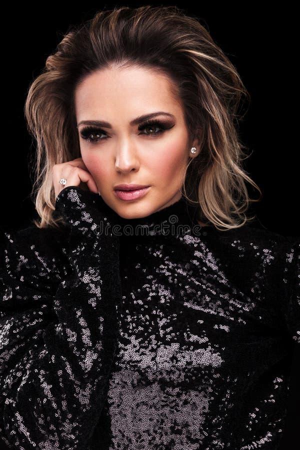De mooie vrouw in zwarte glanzende kleding kijkt aan kant stock foto
