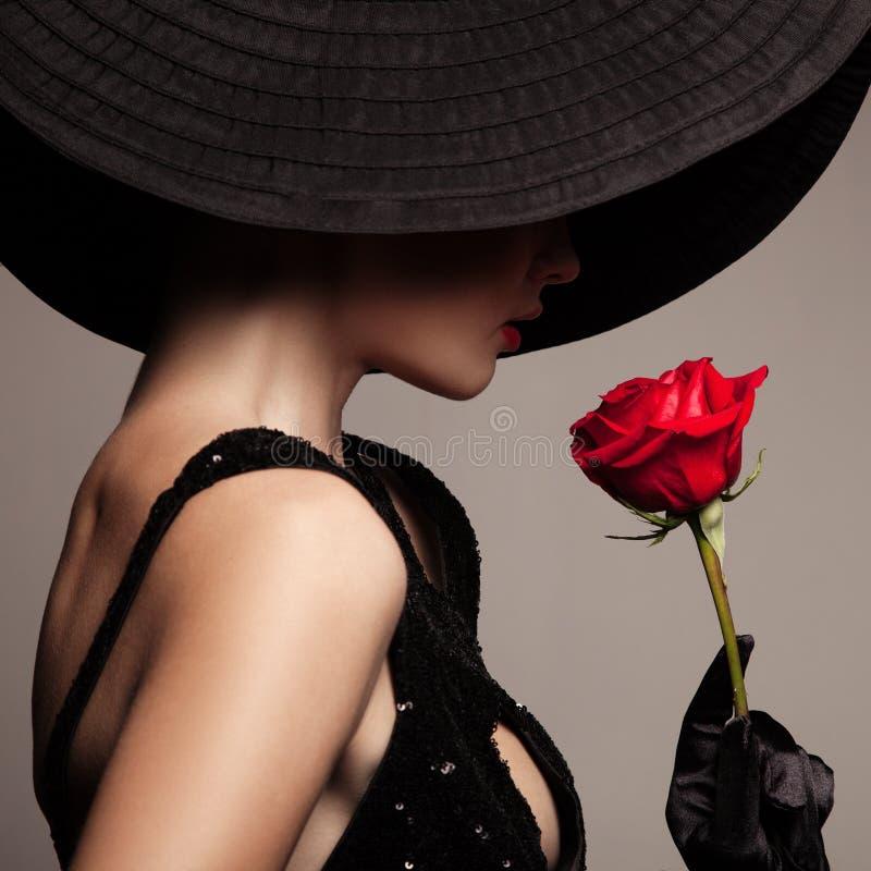 De mooie vrouw in zwarte hoed en rood nam toe royalty-vrije stock foto