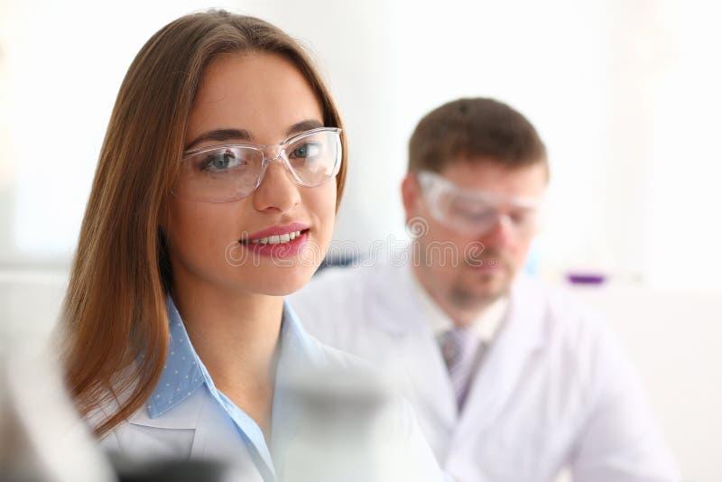 De mooie vrouwelijke chemicus beschermende brillen van het artsenportret in laboratorium royalty-vrije stock afbeeldingen