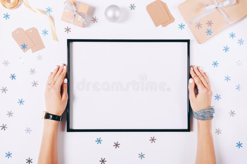 De mooie vrouwelijke handen houden het lege kader stock fotografie