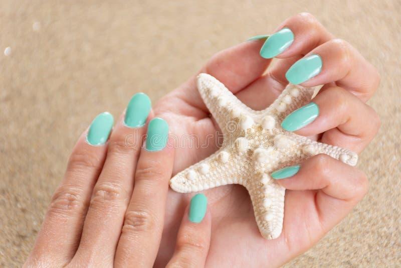 De mooie vrouwelijke handen met een turkoois kleuren de holdingszeester van het spijkerspoetsmiddel en overzees zand op de achter stock fotografie