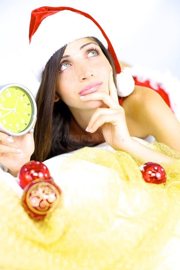 De mooie vrouwelijke Kerstman die over Kerstmis met hoogtepunten denkt royalty-vrije stock afbeelding