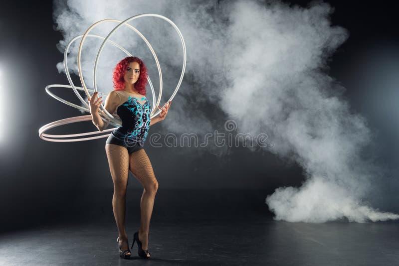 De mooie vrouwelijke rode hoepels van de de kunstenaarsholding van het haarcircus stock afbeeldingen