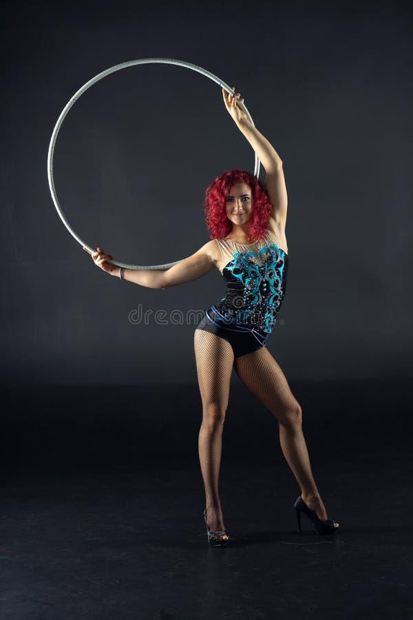 De mooie vrouwelijke rode kunstenaar van het haarcircus met een hoepel royalty-vrije stock afbeeldingen