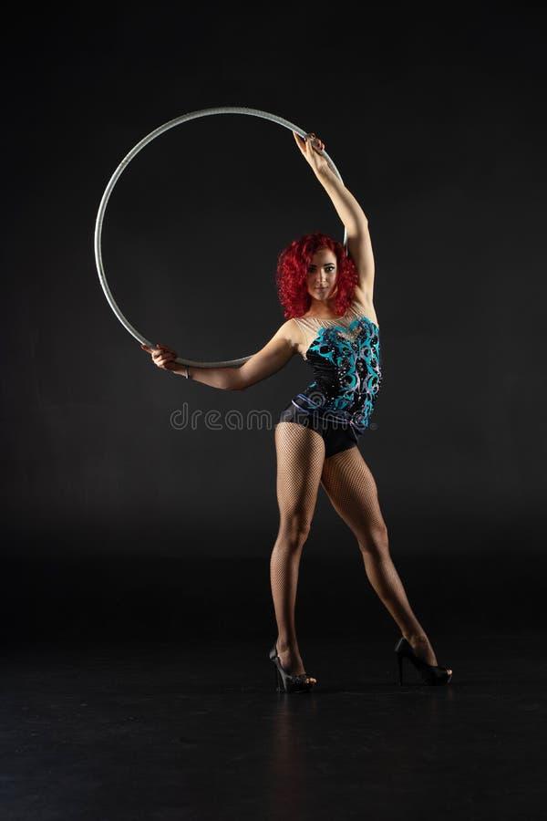 De mooie vrouwelijke rode kunstenaar van het haarcircus met een hoepel stock fotografie