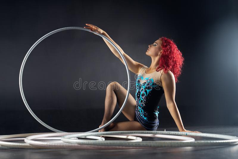 De mooie vrouwelijke rode kunstenaar van het haarcircus met hoepels stock foto