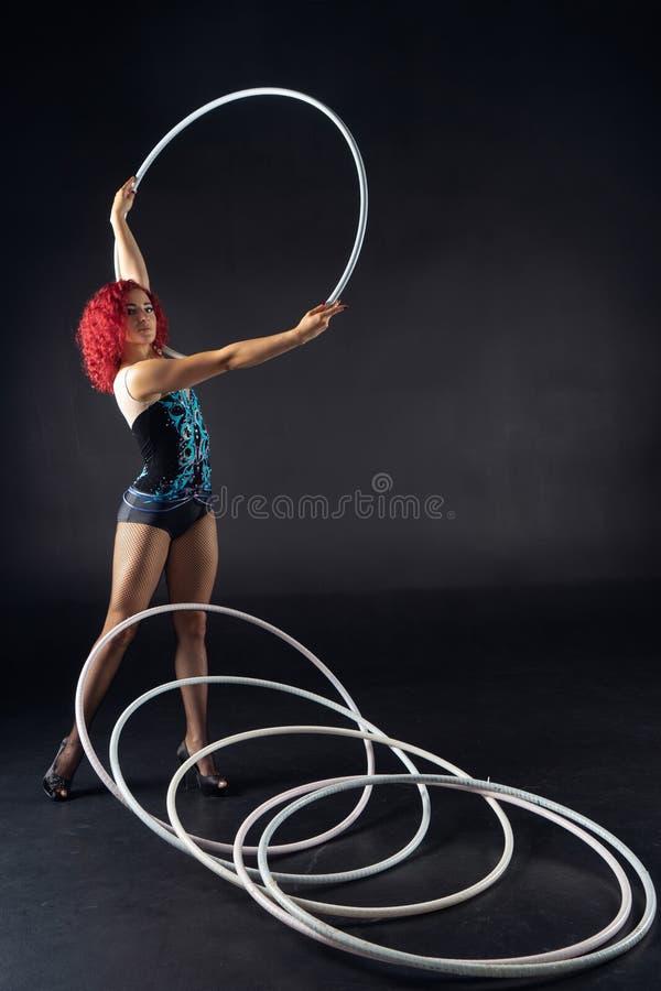 De mooie vrouwelijke rode kunstenaar van het haarcircus met hoepels royalty-vrije stock afbeelding
