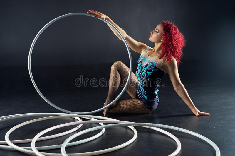 De mooie vrouwelijke rode kunstenaar van het haarcircus met hoepels stock afbeelding