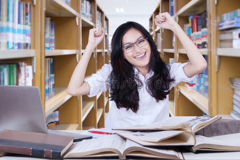 De mooie vrouwelijke student die haar opheffen dient bibliotheek in royalty-vrije stock foto's