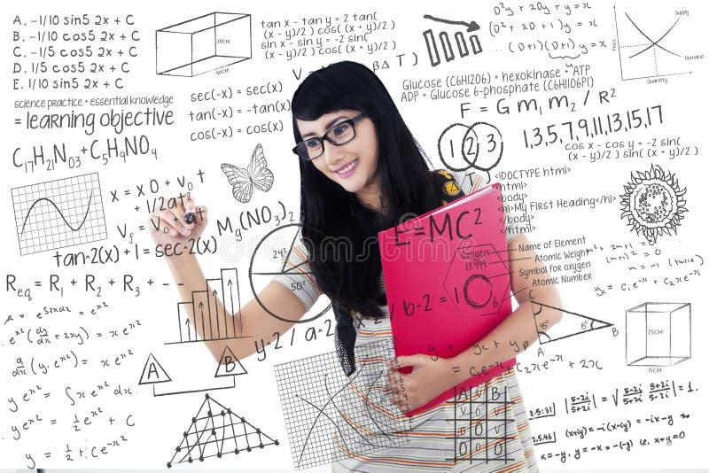 De mooie vrouwelijke student schrijft op transparante witte raad stock afbeeldingen