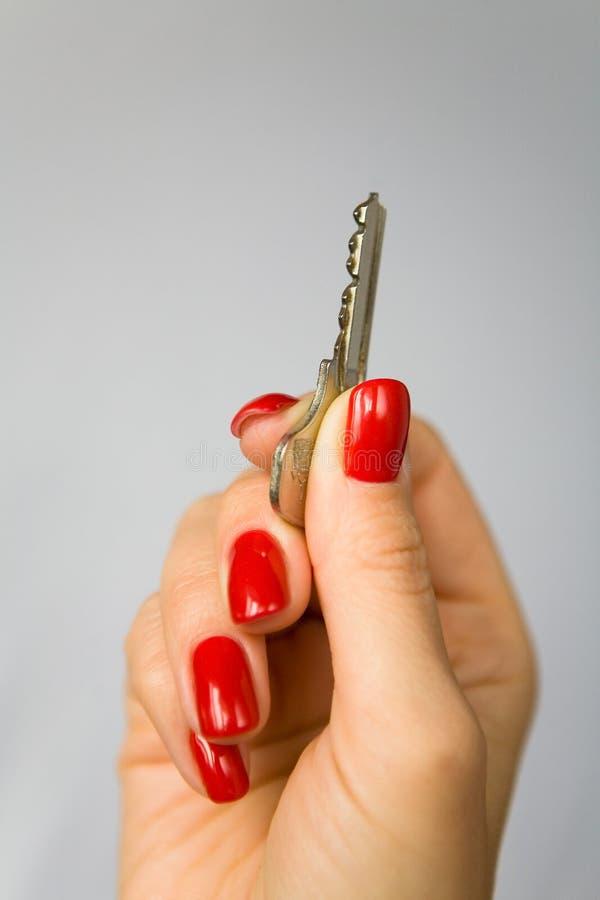 De mooie vrouwelijke vingers met rode spijkers houden de sleutel stock fotografie