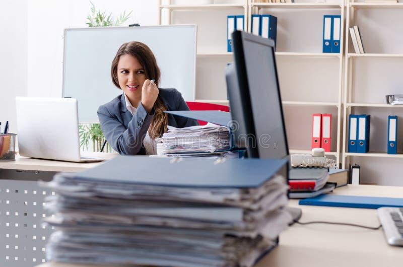 De mooie vrouwelijke werknemer ongelukkig met het bovenmatige werk stock foto