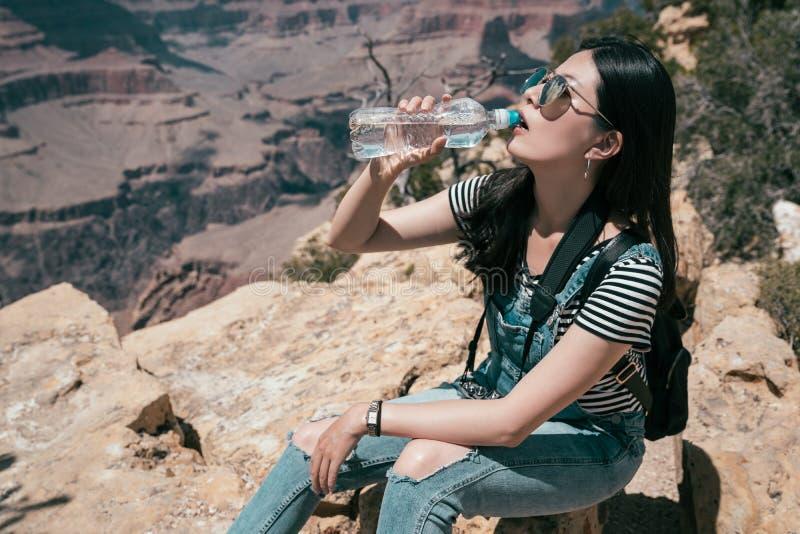De mooie vrouwelijke zitting van de wandelaarreiziger in openlucht royalty-vrije stock fotografie