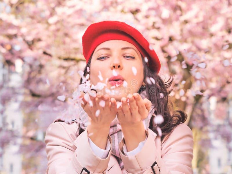De mooie Vrouwen blazende bloemblaadjes in haar handen, sluiten omhoog stock afbeelding