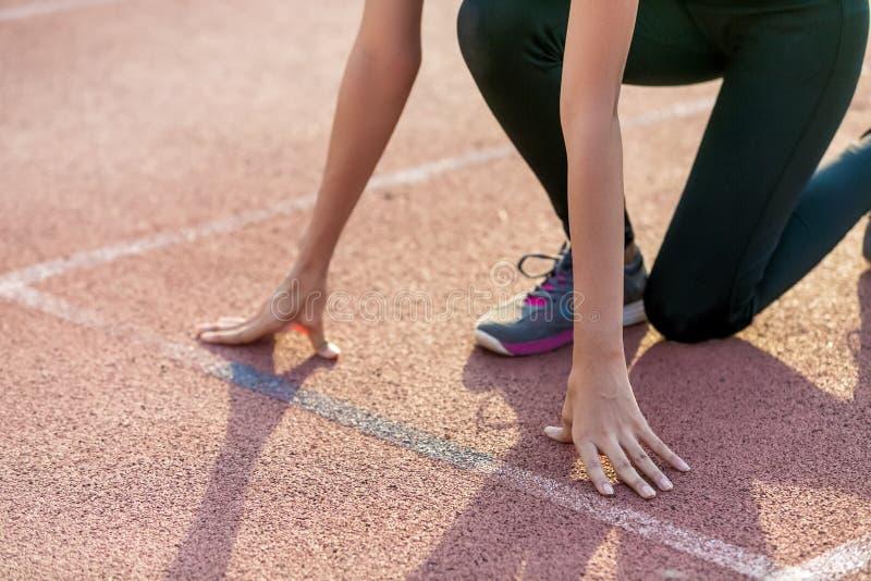 De mooie vrouwenatleet op een rasspoor is bereid te lopen stock foto's