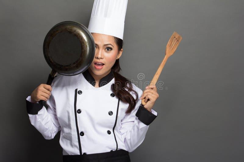 De mooie vrouwenchef-kok heeft pret met haar kokend hulpmiddel stock afbeeldingen
