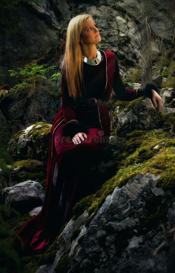 de mooie vrouwenfee met lang blondehaar in een historische toga zit amids moos behandelde rotsen stock afbeeldingen