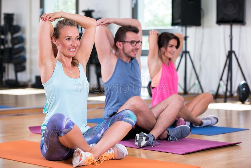 De mooie vrouwenman groep doet sportfitness training in een gymnastiek royalty-vrije stock fotografie