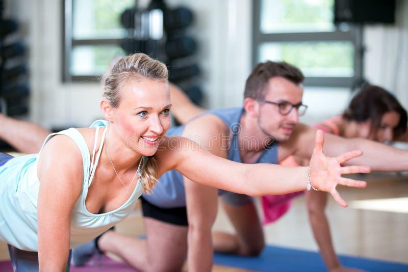 De mooie vrouwenman groep doet sportfitness training in een gymnastiek royalty-vrije stock foto