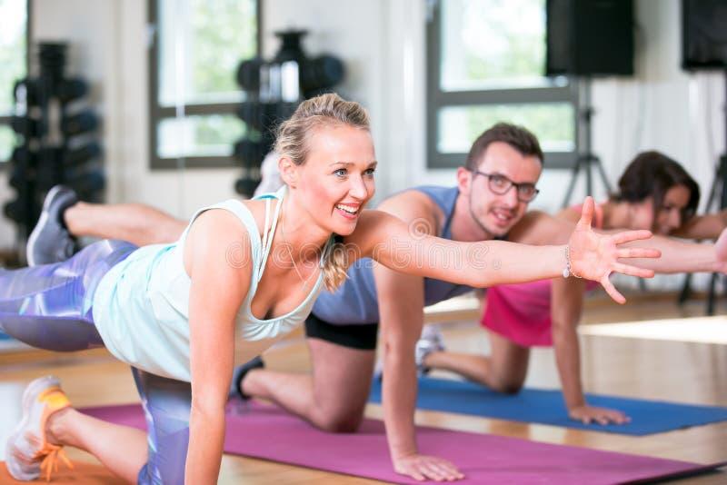 De mooie vrouwenman groep doet sportfitness training in een gymnastiek stock afbeeldingen