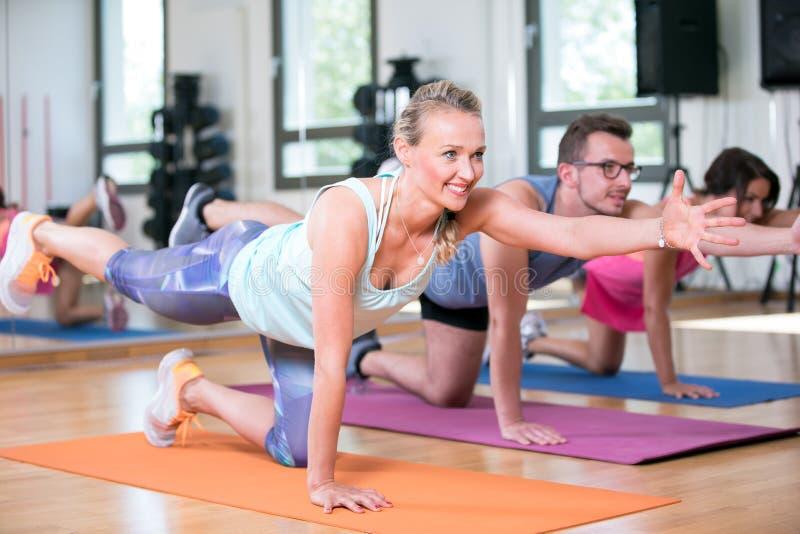 De mooie vrouwenman groep doet sportfitness training in een gymnastiek royalty-vrije stock foto's