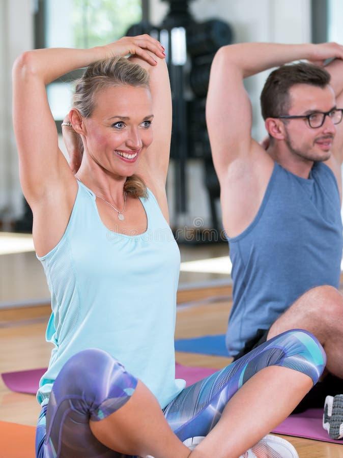 De mooie vrouwenman groep doet sportfitness training in een gymnastiek stock foto