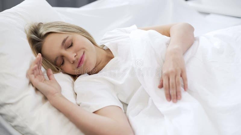 De mooie vrouwenslaap in bed, die goede dromen hebben, die in ochtend rusten, troost stock afbeelding