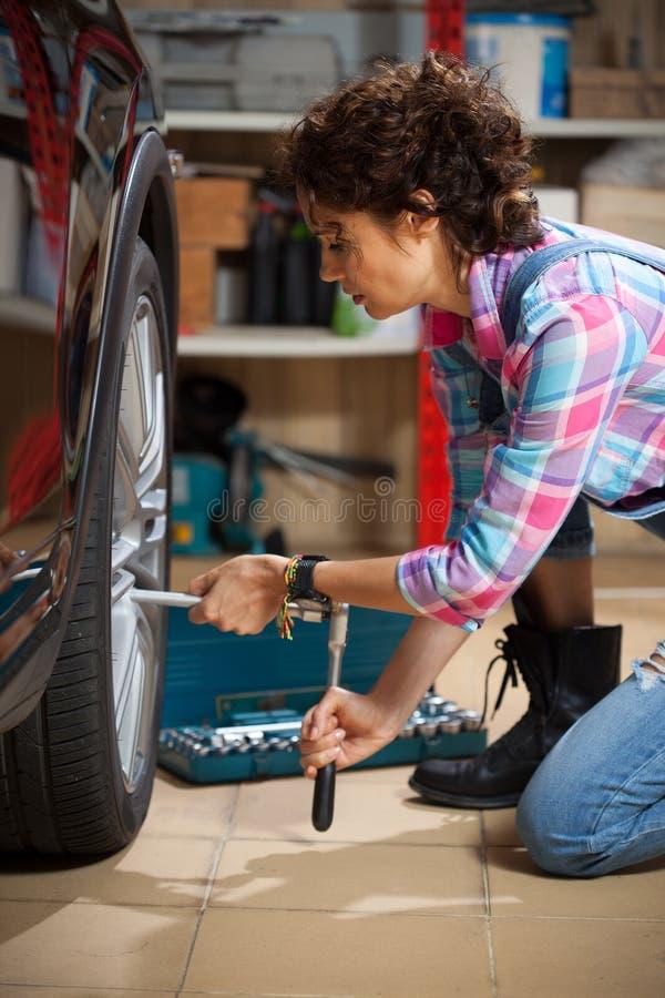 De mooie vrouwenwerktuigkundige in overall haalt de het bevestigen bouten op het wiel van de auto aan royalty-vrije stock afbeeldingen