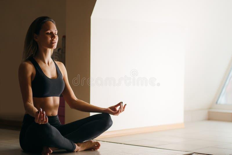 De mooie vrouwenzitting in lotusbloem stelt en mediterend bij yogastudio stock foto's