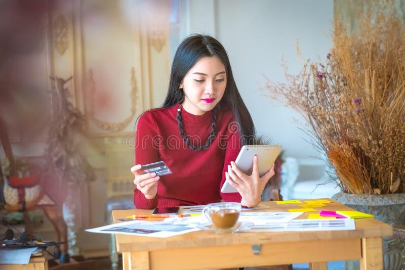 De Mooie vrouwenzitting thuis en winkelend met laptop en stock afbeelding