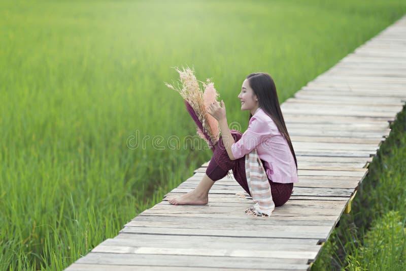 De mooie de vrouwenzitting van Laos alleen met verfraait bloem op houten brug in groen padieveld stock foto's