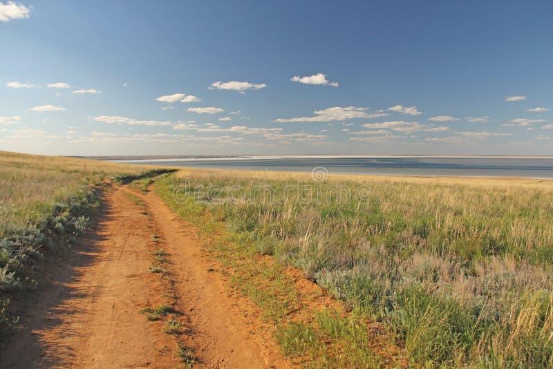 De mooie weg op het gebied, gaat voorbij de horizon Blauwe hemel en groen gras Mooi de zomerlandschap stock foto