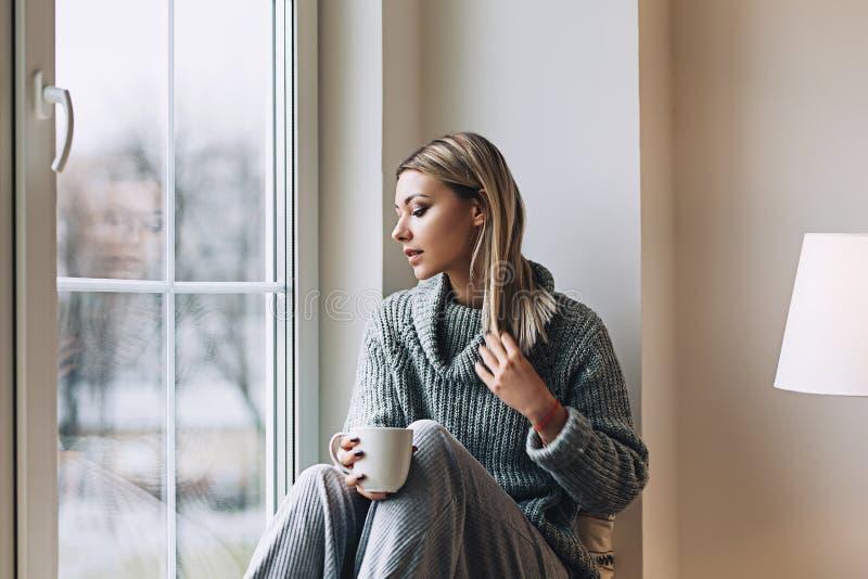 De mooie witte modieuze vrouw in comfortabele Skandinavische interrior zit thuis dichtbij het grote venster, portret van mooi stock afbeeldingen