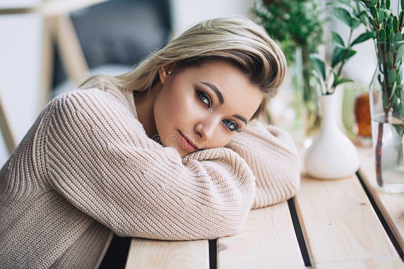 De mooie witte modieuze vrouw in comfortabele Skandinavische interrior zit thuis dichtbij het grote venster, portret van mooi stock foto's