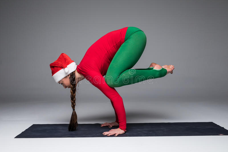 De mooie yogavrouw in de praktijkyoga van de santahoed stelt stock foto