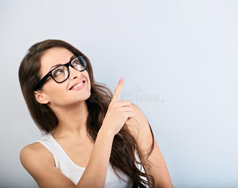 De mooie zaken wekten toevallige vrouw die in oogglazen op de vinger met het toothy glimlachen benadrukken Het portret van de clo stock fotografie